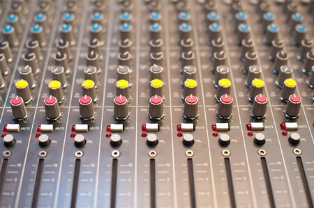 electronic music: Music studio mixer detail of knobs and buttons in selective focus Stock Photo
