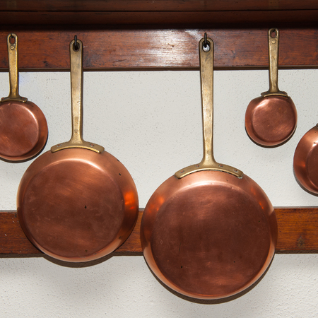 row of vintage copper pans different size hung on wooden shelf in kitchen