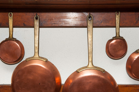 hung: Row of vintage copper pans, different size, hung on wooden shelf in kitchen, detail
