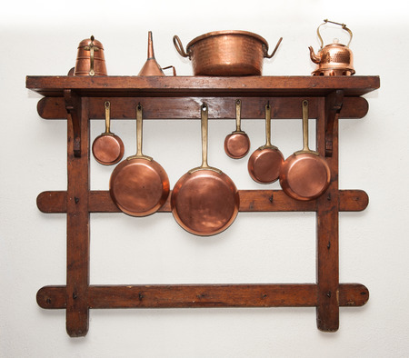 Different kind of vintage copper cookware, pans, coffee pot and funnell hung on wooden shelf in kitchen Stock Photo