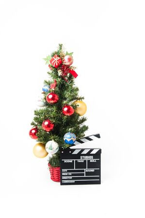 holiday movies: Christmas tree  with red gold and blue balls and cinema movie clapperboard on white background vertical frame