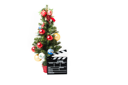holiday movies: Christmas tree  with red gold and blue balls and cinema movie clapperboard on white background