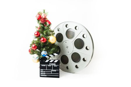 holiday movies: Christmas tree  with red gold and blue balls, cinema big reel and movie clapperboard on white background