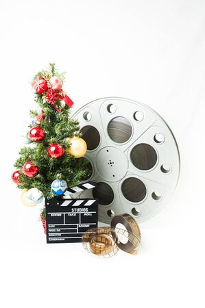 holiday movies: Christmas tree  with red gold and blue balls, cinema big reel and movie clapperboard on white background vertical frame