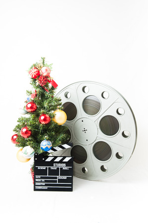 christmas movies: Christmas tree  with red gold and blue balls, cinema big reel and movie clapperboard on white background vertical frame