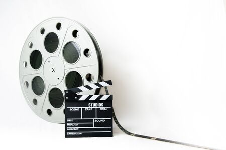 35mm: 35mm cinema big reel with filmstrip unrolled and movie clapperboard on white background Stock Photo