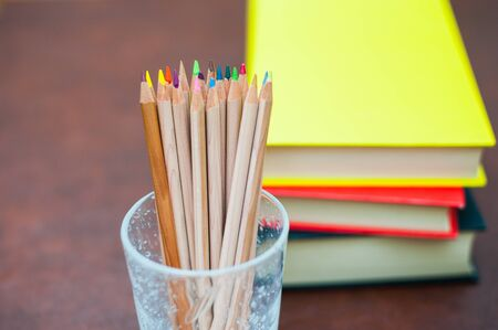 pen holder: Colored pencils in glass pen holder with pile of books out of focus in background,  yellow cover, vertical frame