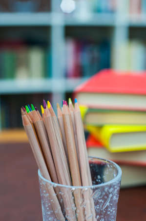 pen holder: Colored pencils in glass pen holder with pile of books out of focus in background, vertical frame