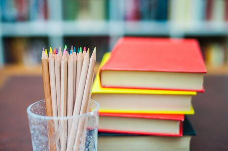 pen holder: Colored pencils in glass pen holder with pile of books out of focus in background Stock Photo