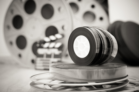 black out: Heap of old 35 mm movie reels with out of focus clapper and boxes in background, vintage black and white Stock Photo