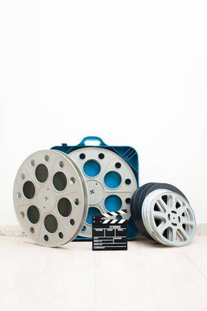 35 mm: Movie clapper board and 35 mm cinema reels with film and blue box Stock Photo