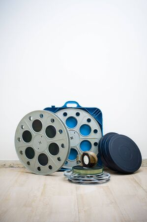 35 mm: Heap of old 35 mm cinema movie reels with blue professional boxes, vertical frame
