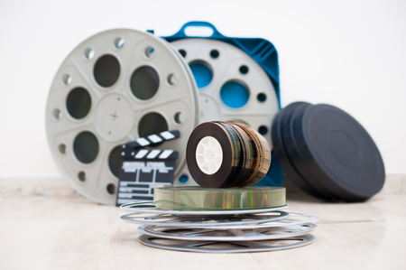 35: Heap of old 35 mm movie reels with out of focus clapper and boxes in background Stock Photo