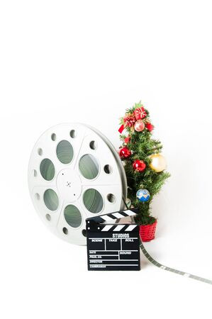 christmas movies: Movie clapper board and reel with christmas tree Stock Photo