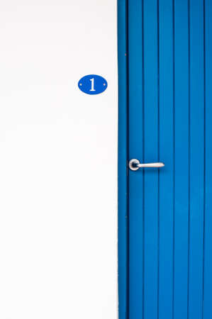 copyspace: Number one blue door part white wall with copyspace