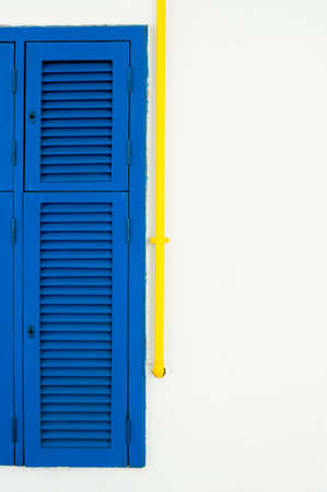 white wall: Part of blue shutter window and yellow tube on white wall with copyspace