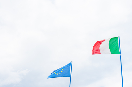 european community: Italian and european community flag on cloudy sky with copy space