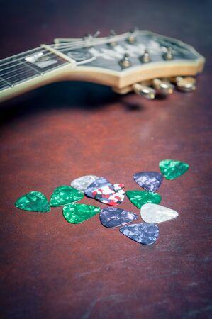 gitara: Wiele kostki do gitary Plectrum w różnych kolorach z głową gitarową nieostry w tle Zdjęcie Seryjne