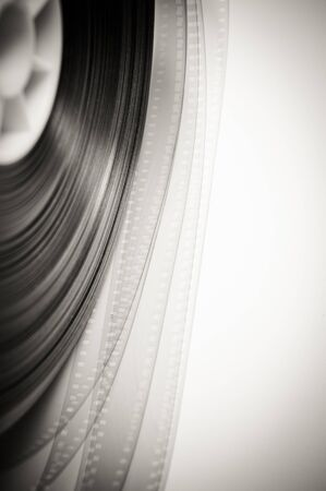 35 mm: 35 mm film detail with movie reel in black and white Stock Photo