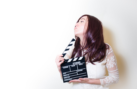 audition: Young beautiful cinema actress with movie clapper board portrait