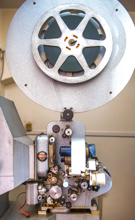 16mm: Rome, Italy - April 22 2015. Vintage professional 16 mm cinema movie projector  with rolled film Editorial