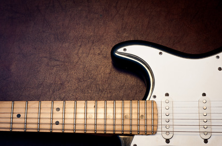 fret: Electric guitar body and neck detail on wooden background vintage look