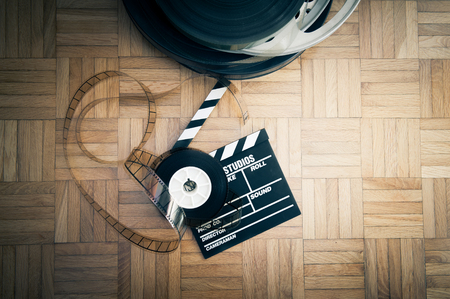 cinema film: Cinema movie clapper board and 35 mm film reel on wooden floor vintage color effect Stock Photo