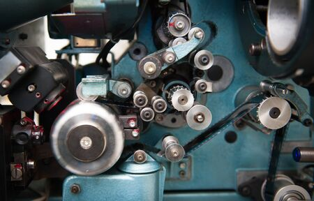 35 mm: 35 mm movie cinema projector detail with spool and film running, close up in selective focus