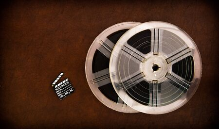 super 8: Little movie clapper board and transparent film reels on brown table
