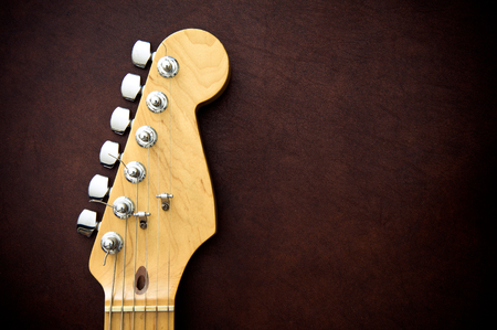 fret: Electric guitar head and neck detail on wooden background vintage look