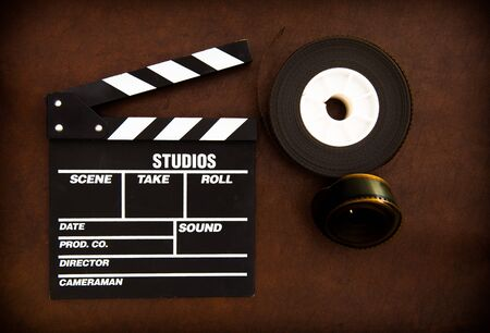35 mm: Movie clapper board and 35 mm film reels detail on brown table