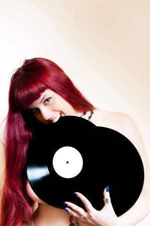 discoteque: Young woman smiling and biting analog vinyl records