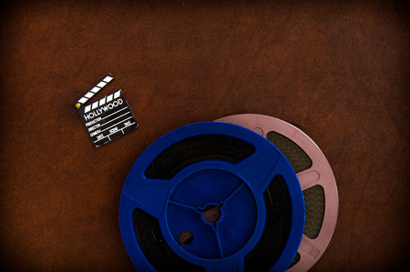 super 8: Little movie clapper board detail and colored film reels on brown table