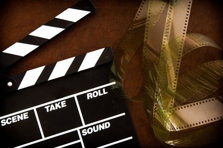 filmstrip: Movie clapper board detail and unrolled  filmstrip on brown table
