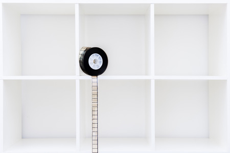35 mm: 35 mm film reel and filmstrip on white cubical bookshelf with empty copy space