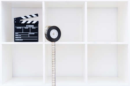 35 mm: Movie clapper board and 35 mm film reel on white cubical bookshelf with empty copy space