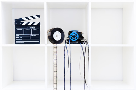 super 8: Movie clapper board and film reels on white cubical bookshelf with empty copy space