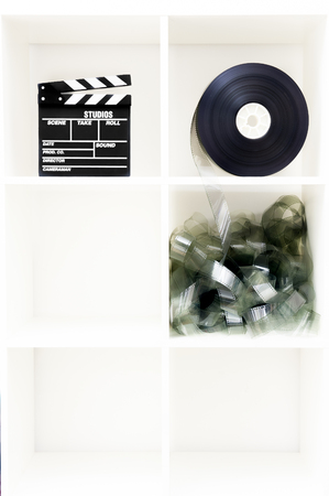 cubic: Movie clapper board and film reel on vertical white bookshelf with six cubic boxes and copy space Stock Photo