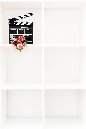 christmas movies: Movie clapper board with christmas decoration on vertical white bookshelf with six cubic boxes and copy space