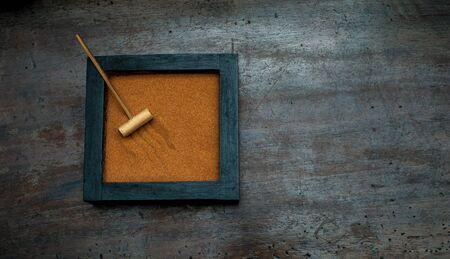 scraped: Zen garden base with rake and orange sand on aged scraped wood Stock Photo