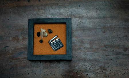 scraped: Zen garden with stones and movie clapper board, orange sand on aged scraped wood