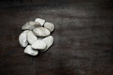 scraped: Heap of white pebble stones on aged and scraped wood