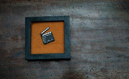 scraped: Zen garden with movie clapper board, orange sand on aged scraped wood