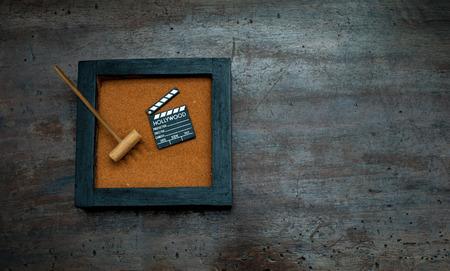 scraped: Zen garden with rake and movie clapper board, orange sand on aged scraped wood Stock Photo