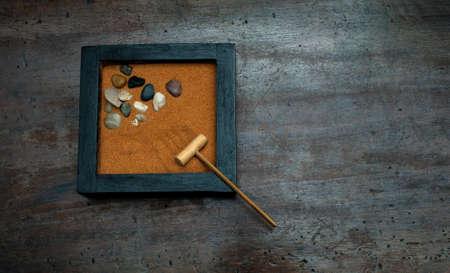 scraped: Zen garden with rake and stones, orange sand on aged scraped wood Stock Photo