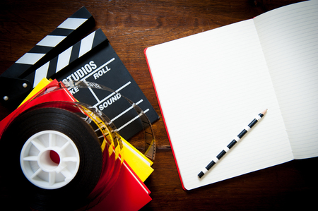 Screenwriter desktop detail with clapper, film reel notebook and pencil