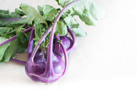 celeriac: Couple of raw unusual purple celeriac roots on table with foliage