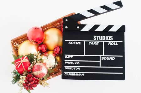holiday movies: Movie clapper board and christmas decoration red and golden on white background