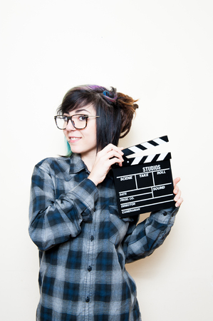 audition: Smiling teen woman with movie clapper board on white