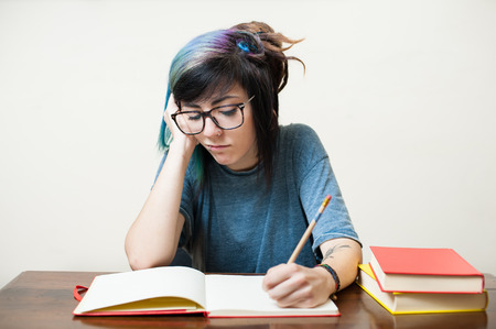 coed: Young studying female student at desktop with red and yellow books